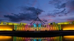 Parliament House in Canberra lit up with rainbow coloured lights.